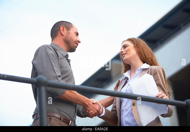 Businessman and business woman shaking hands - Stock-Bilder