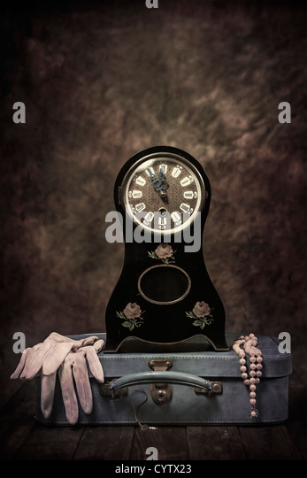 an old table clock in Biedermeier style with a leather suitcase, gloves and a pearl necklace - Stock-Bilder