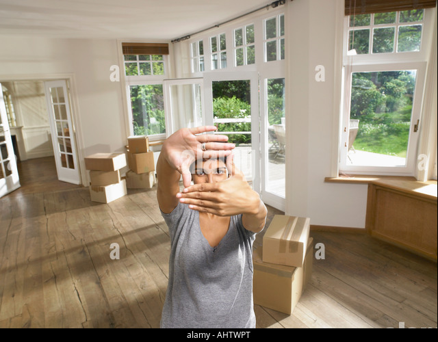 Women framing face while moving into empty house. - Stock Image