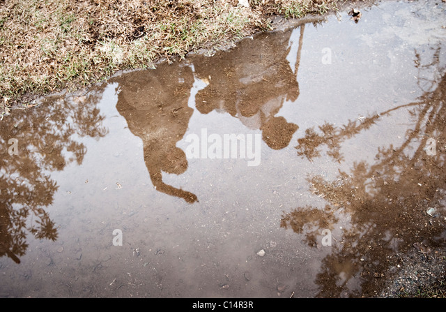 Two young men point out distant mountain ranges as they are reflected in a puddle. - Stock Image