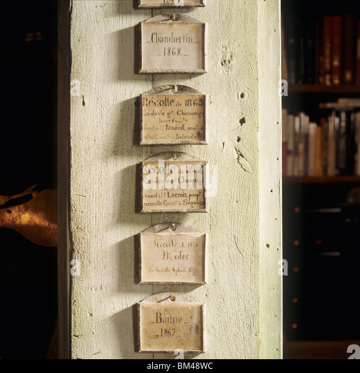 antique wine cellar labels nailed to a wooden column - Stock Image