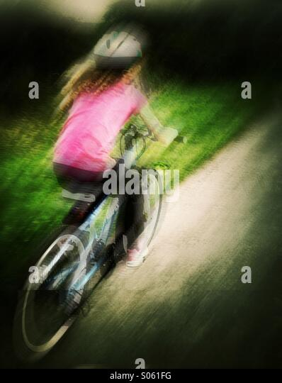 Young girl cycling with motion blur - Stock Image