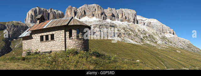 Church on the green grass at the foot of the massif of the Sella mountain range and blue sky in the background - Stock Image