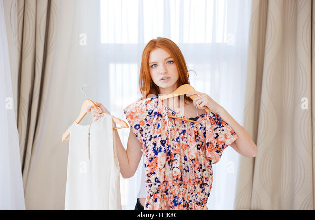 Thoughtful attractive young woman choosing clothes and deciding what to put on - Stock Image
