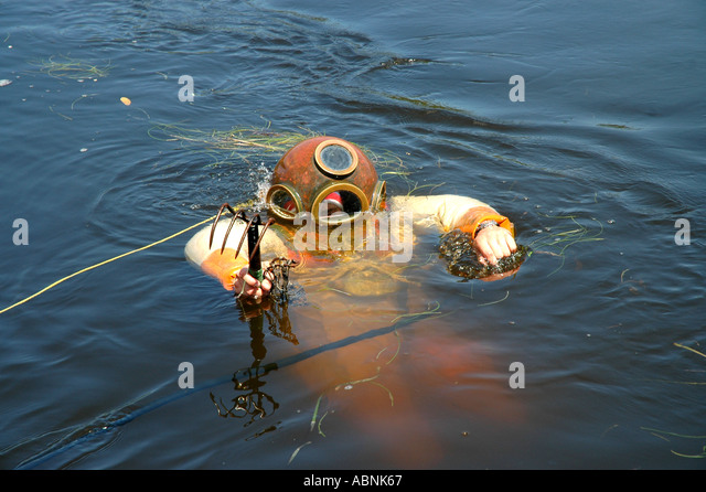 Tarpon Springs Florida sponge diving demonstration diver floating on surface with sponge - Stock Image