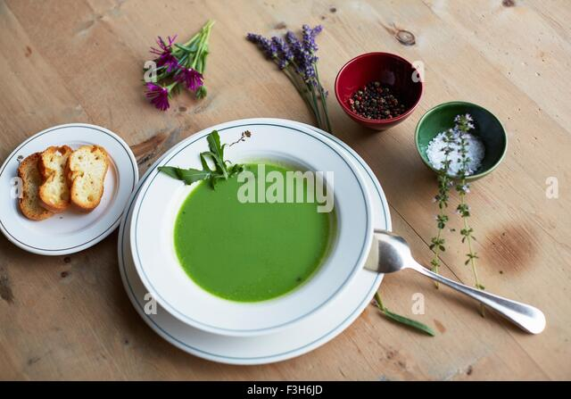 Table with fresh green soup and bread - Stock Image