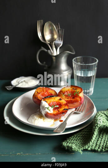Plate with grilled peach with greek yogurt and honey and decorated with fresh thyme - Stock Image