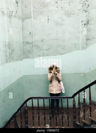High Angle View Of Woman Holding Smart Phone Against Wall On Steps - Stock Image