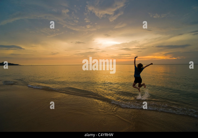 A young woman jumping for joy and celebrating on the beach at sunset. Taken on Phra Ae Beach, Koh Lanta, South Thailand - Stock Image