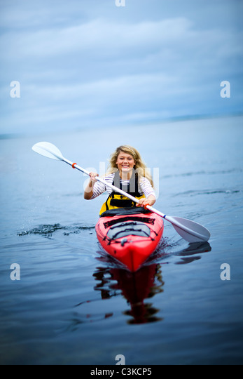 Teenage girl rowing canoe on lake, smiling - Stock Image