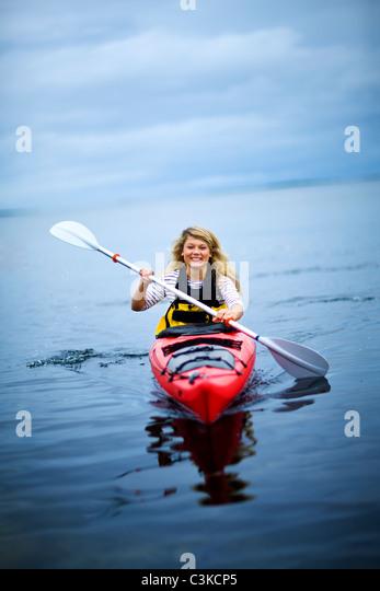 Teenage girl rowing canoe on lake, smiling - Stock Image