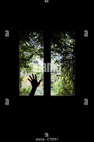 Silhouette hand against Glass windows in a front door in front of a Overgrown garden view. UK - Stock Image