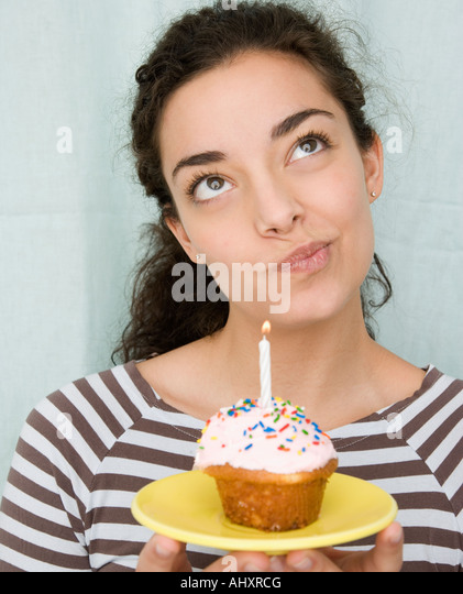 Woman holding cupcake with candle - Stock Image