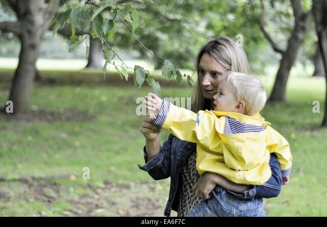 Mother and son looking at leaf - Stock Image