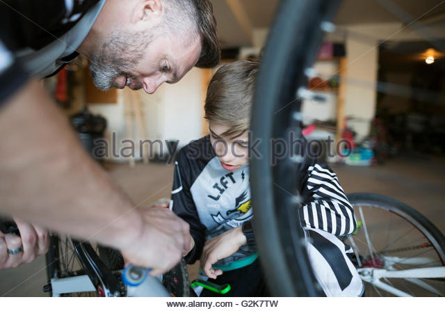 Father and son repairing bicycle - Stock Image