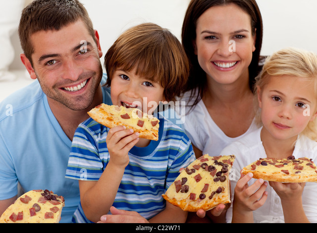 Portrait of family eating pizza in living-room - Stock Image