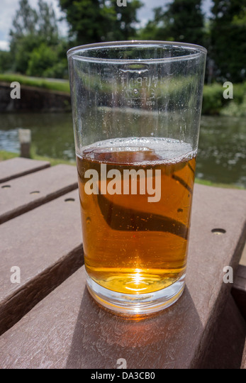 Glass of Beer beside a canal. Canalside Pub - Stock Image
