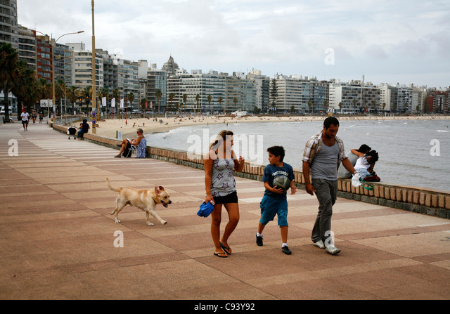 People walking along the Rambla, the city's riverfront promenade, Montevideo, Uruguay. - Stock Image