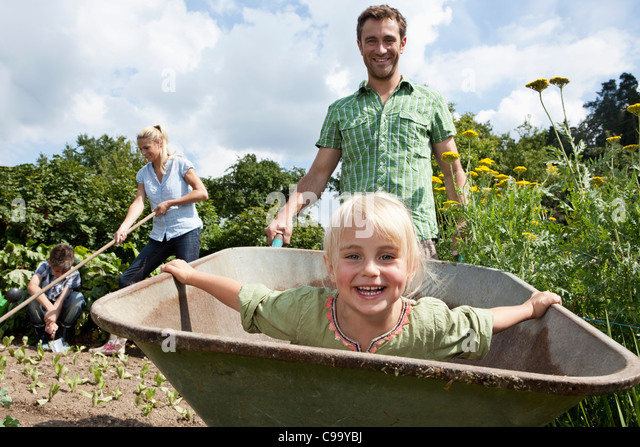 Germany, Bavaria, Altenthann, Family gardening together in garden - Stock Image
