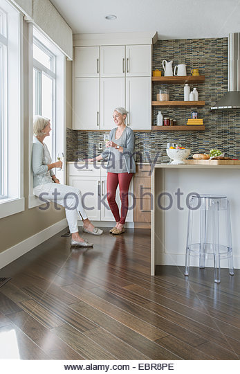 Women drinking wine and talking in kitchen - Stock Image