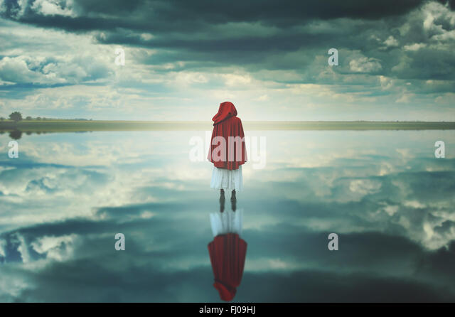 Red hooded woman in a strange landscape with clouds. Fantasy and surreal - Stock-Bilder