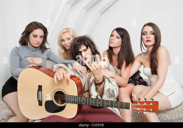 Young male guitarist with cool gesture surrounded by female friends - Stock-Bilder