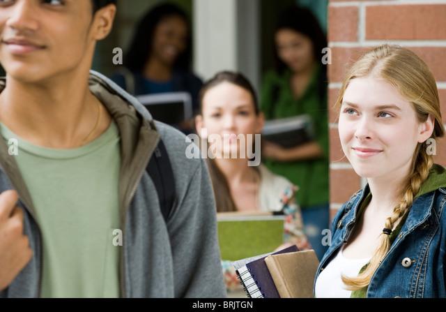 Young woman admiring student walking past - Stock-Bilder
