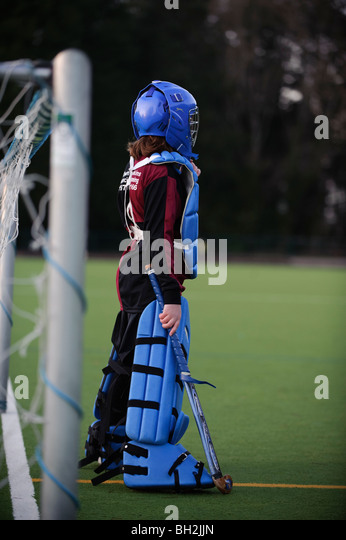 11 year old girl wearing protective padding in goal playing hockey on all-weather surface, UK - Stock Image