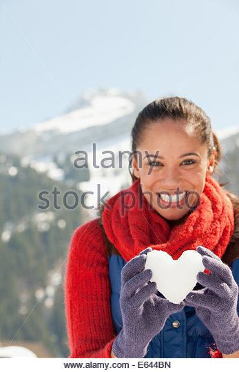 Portrait of smiling woman holding heart-shape snowball - Stock-Bilder