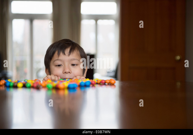 Boy peering over table at candy - Stock Image