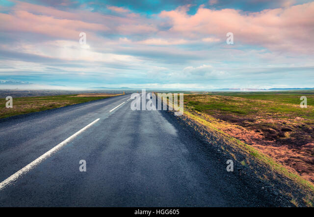 Empty asphalt road with colorful cloudy sky. Beautiful outdoor scenery in Iceland, Europe. Image of travel concept - Stock Image