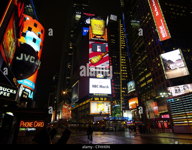 A wet street reflects the signs at Times Square, New York city, at night - Stock Image