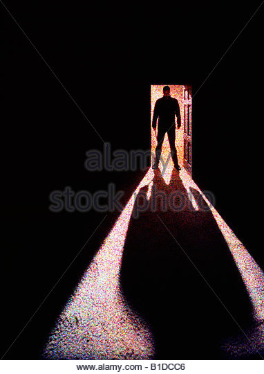 A menacing silhouette of a man holding a knife, in a doorway. - Stock-Bilder