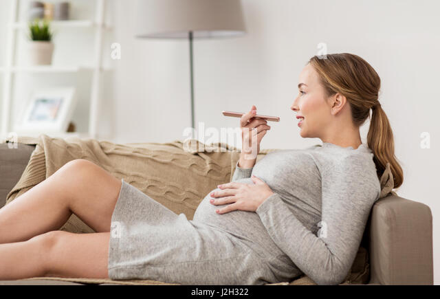 pregnant woman using voice recorder on smartphone - Stock Image