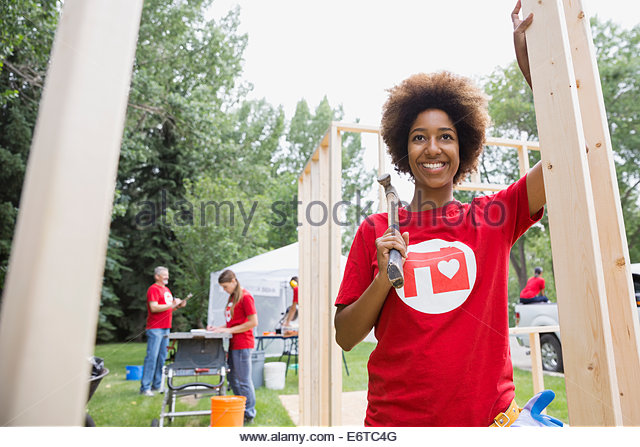 Portrait of confident volunteer at construction frame - Stock Image
