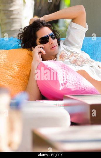 Young man lying on a couch and talking on the mobile phone - Stock-Bilder