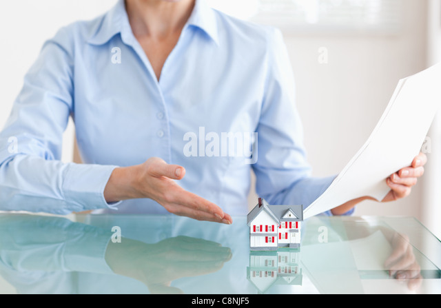 Woman holding papers showing a model house - Stock Image