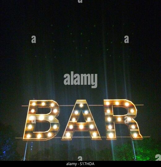 A bar sign outside against a dark sky - Stock Image
