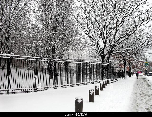 Snowy urban sidewalk by a fence with pedestrians in the distance. - Stock Image