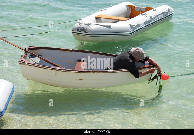 St Ives, Cornwall, UK:  Man in Rowing Boat untying rope in St Ives Harbour. - Stock Image