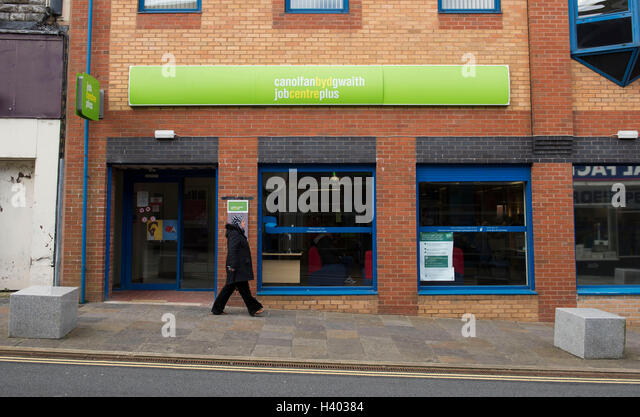 A woman walks passed a job centre in Blackwood, South Wales. - Stock Image