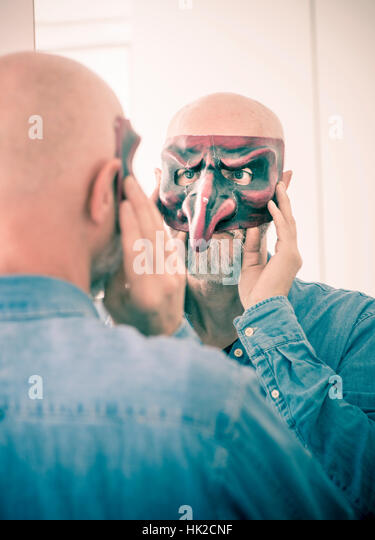 Old man cover face with carnival mask. Looking at himself in a mirror. Concept of ageing, self image as a senior - Stock-Bilder