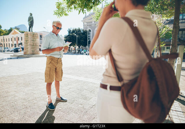 Senior man being photographer by a woman in the city during their vacation. Senior couple taking photos on their - Stock-Bilder