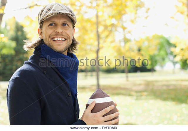 Happy mid adult man playing American football at park - Stock Image