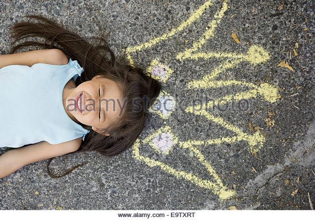 Enthusiastic girl with sidewalk chalk crown overhead - Stock Image