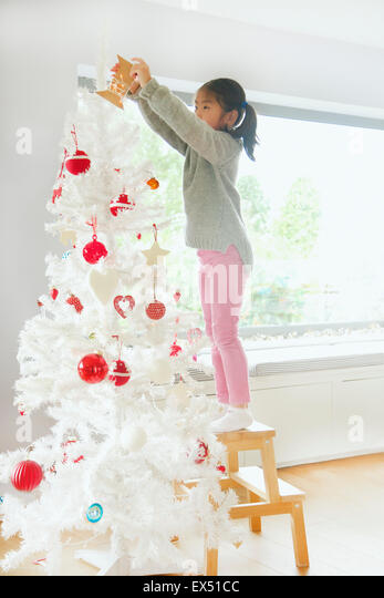 Young Girl Decorating Christmas Tree - Stock Image