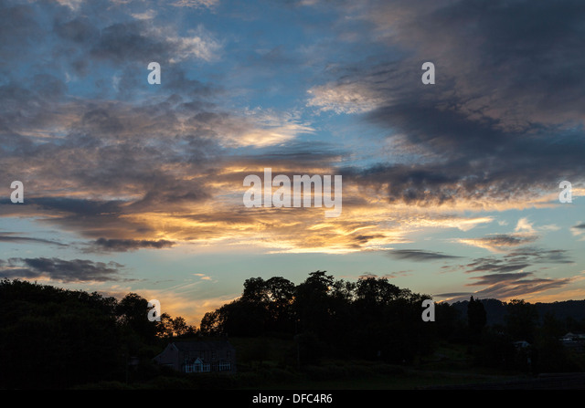 EVENING SKY WITH DRAMATIC CLOUDS UK . Trees silhouetted against sky. UK - Stock Image