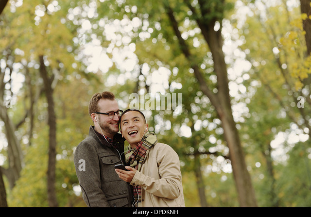Gay couple hugging in park - Stock Image