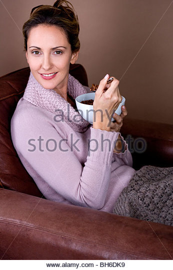 A mid adult woman eating a bowl of cereal - Stock-Bilder