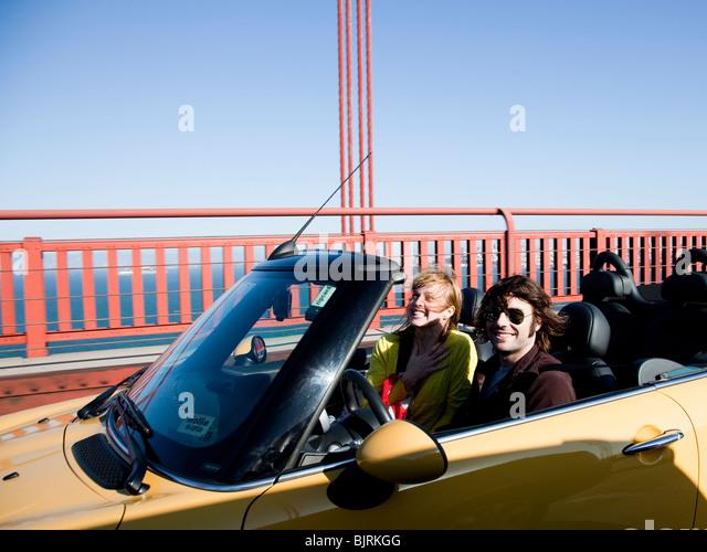 USA, California, San Francisco, young couple passing Golden Gate Bridge in convertible car - Stock Image